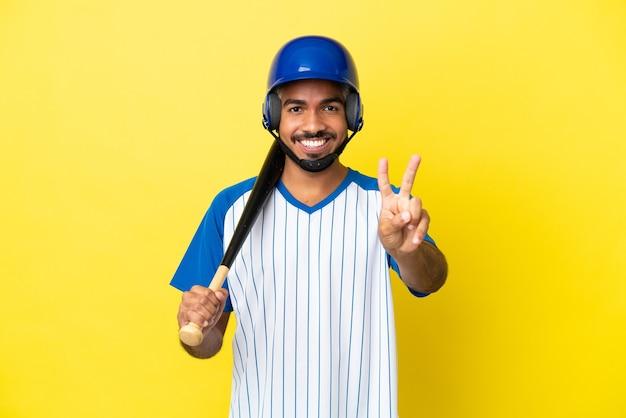 笑顔と勝利の兆候を示す黄色の背景に分離された野球をしている若いコロンビアのラテン男性
