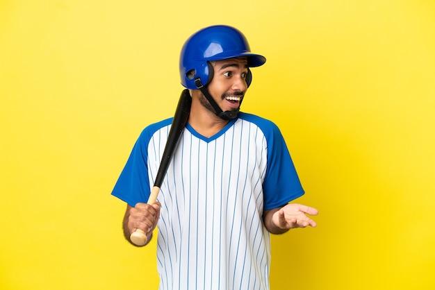 側を見ながら驚きの表情で黄色の背景に分離された野球をしている若いコロンビアのラテン男