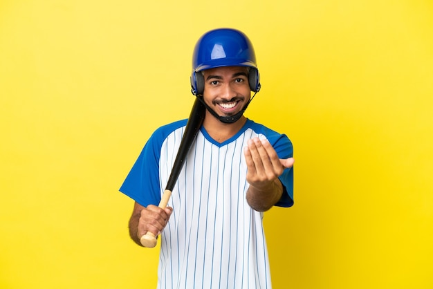 Young colombian latin man playing baseball isolated on yellow background inviting to come with hand. happy that you came