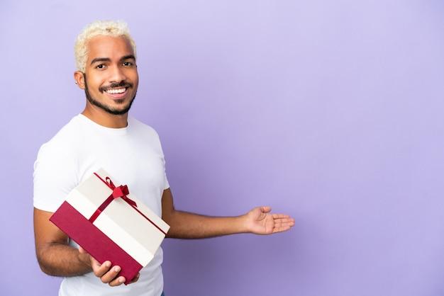 Молодой колумбиец держит подарок на фиолетовом фоне, протягивая руки в сторону, приглашая приехать