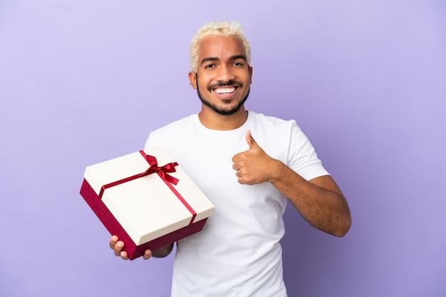 Молодой колумбийский мужчина держит подарок на фиолетовом фоне, показывая жест рукой вверх