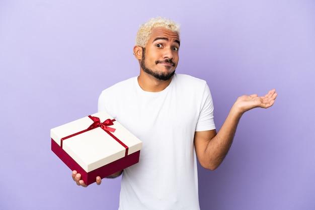 Молодой колумбийский мужчина держит подарок на фиолетовом фоне, сомневаясь, поднимая руки