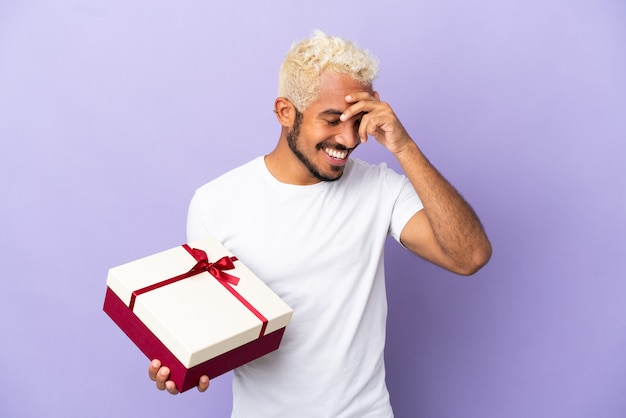 Молодой колумбийский мужчина держит подарок, изолированные на фиолетовом фоне смеясь