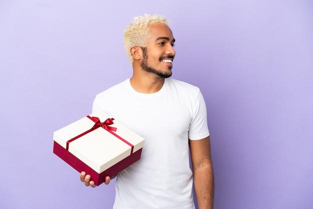 Молодой колумбийский мужчина держит подарок на фиолетовом фоне, глядя в сторону