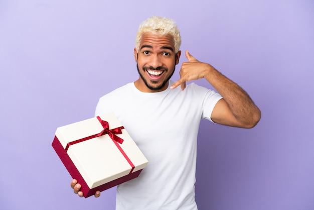 電話ジェスチャーを作る紫色の背景に分離された贈り物を保持している若いコロンビア人。コールバックサイン
