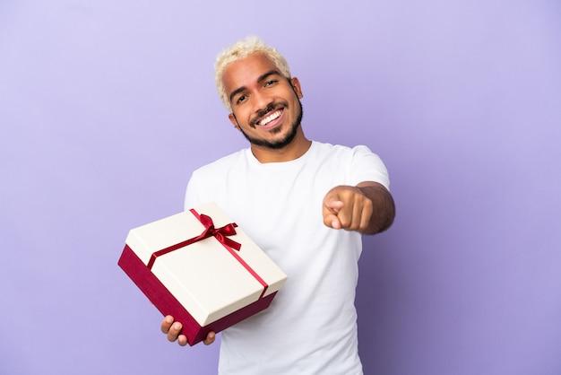 Молодой колумбийский мужчина держит подарок на фиолетовом фоне, указывая спереди с счастливым выражением лица