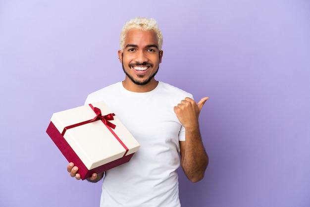 Молодой колумбиец держит подарок на фиолетовом фоне, указывая в сторону, чтобы представить продукт