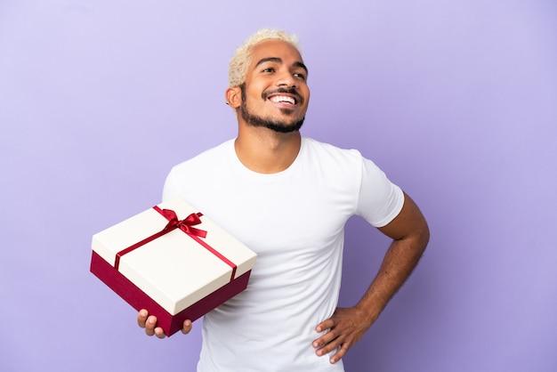Молодой колумбийский мужчина держит подарок на фиолетовом фоне, позирует с руками на бедрах и улыбается
