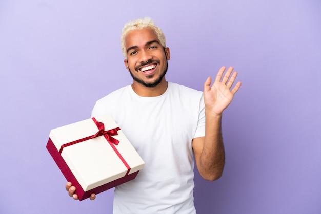 Молодой колумбийский мужчина держит подарок на фиолетовом фоне, салютуя рукой с счастливым выражением лица