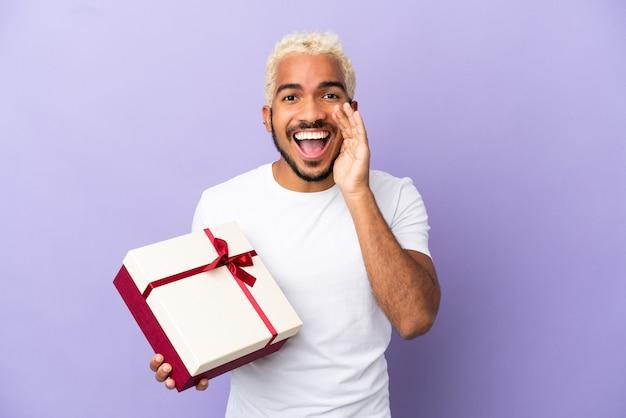 Молодой колумбийский мужчина держит подарок на фиолетовом фоне и кричит с широко открытым ртом