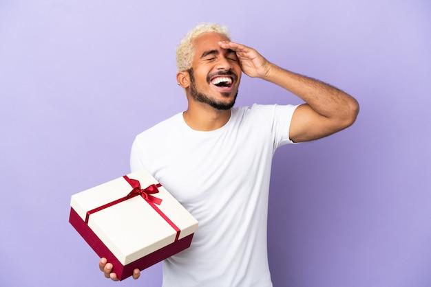 Молодой колумбийский мужчина держит подарок на фиолетовом фоне, много улыбаясь