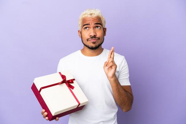 Молодой колумбиец держит подарок на фиолетовом фоне со скрещенными пальцами и желает всего наилучшего