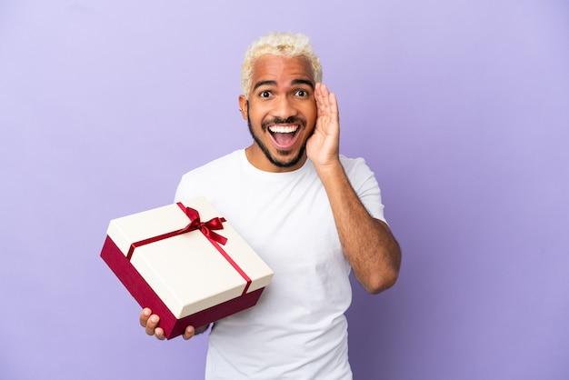 Молодой колумбиец держит подарок на фиолетовом фоне с удивленным и шокированным выражением лица