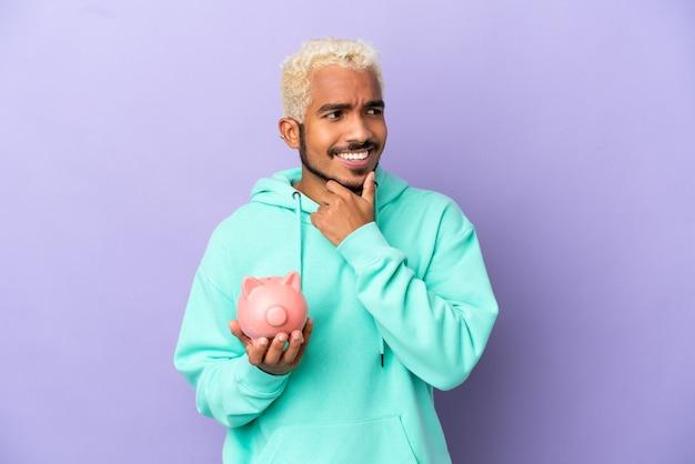 Молодой колумбийский мужчина держит копилку, изолированную на фиолетовом фоне, смотрит в сторону и улыбается