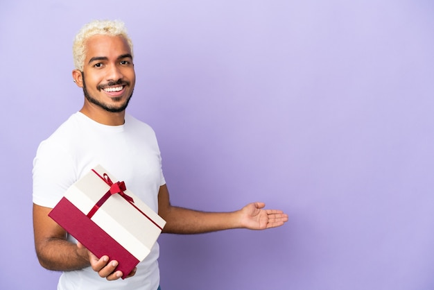 Young colombian man holding a gift isolated on purple background extending hands to the side for inviting to come