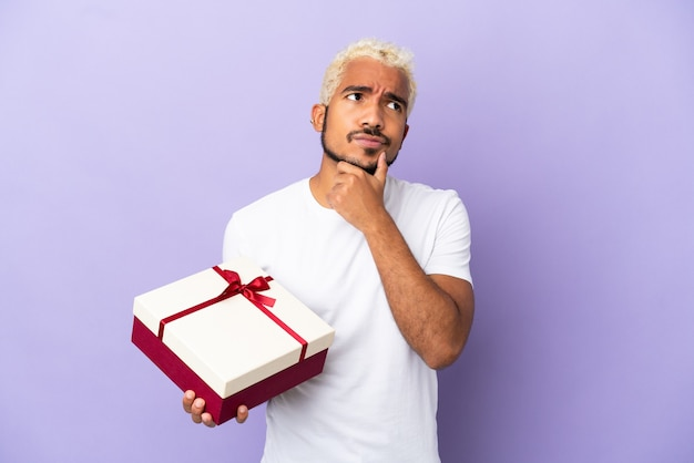 Young colombian man holding a gift isolated on purple background having doubts