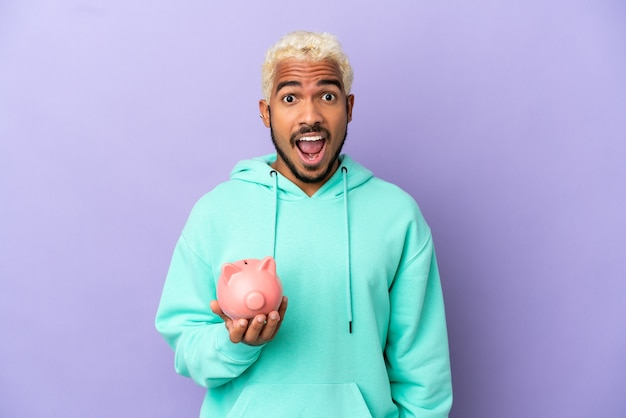 Young colombian man holding a piggybank isolated on purple background with surprise facial expression
