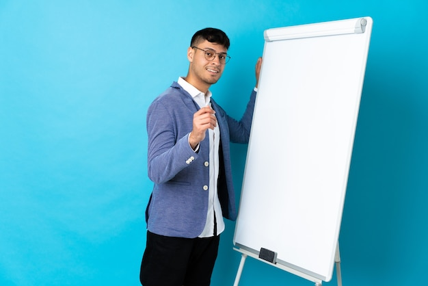 ホワイトボードでプレゼンテーションを行う青で孤立した若いコロンビア人