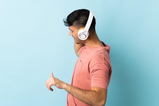 Молодой колумбийский мужчина изолирован на синем, слушает музыку и танцует