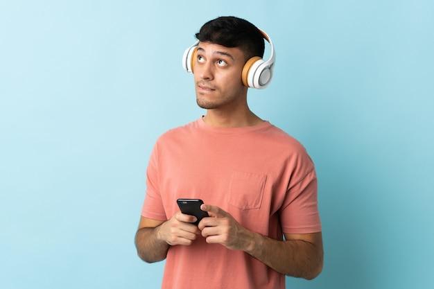 携帯電話と思考で音楽を聴く青いに孤立した若いコロンビア人
