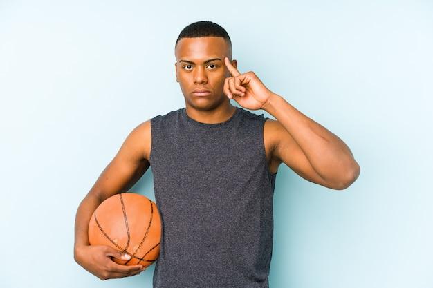 Молодой колумбийский человек, играющий в баскетбол, изолировал указательный храм пальцем, думая, сосредоточенный на задаче.