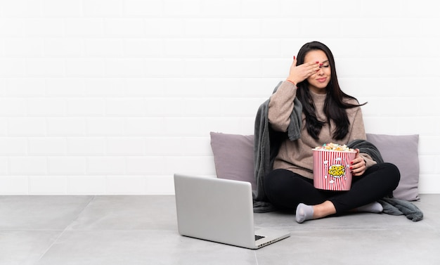 Young colombian woman holding a bowl of popcorns and showing a film in a laptop covering eyes by hands
