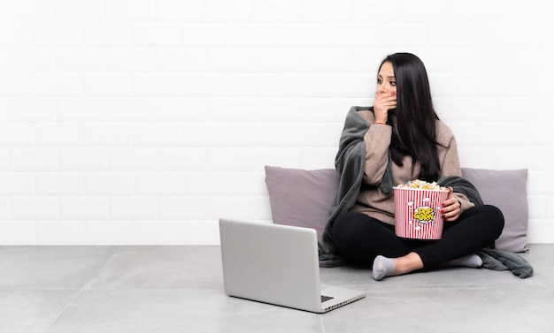 Young colombian woman holding a bowl of popcorns and showing a film in a laptop covering mouth and looking to the side