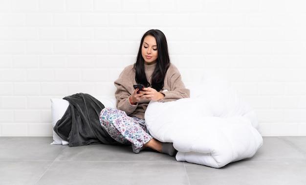 Молодая колумбийская женщина в пижаме в помещении отправляет сообщение с мобильного