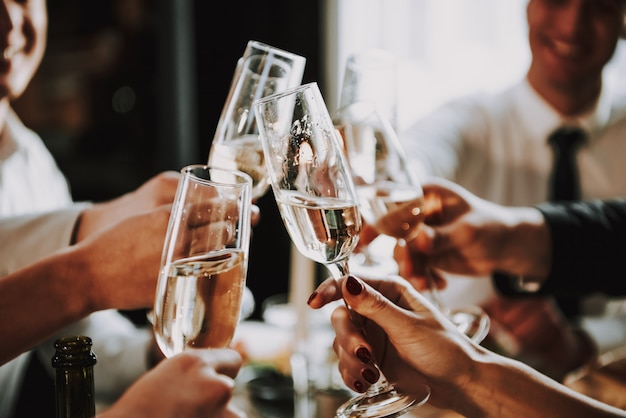 Young company clink champagne glasses on party
