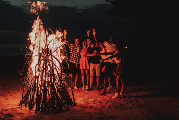 Young company dancing around bonfire on beach.