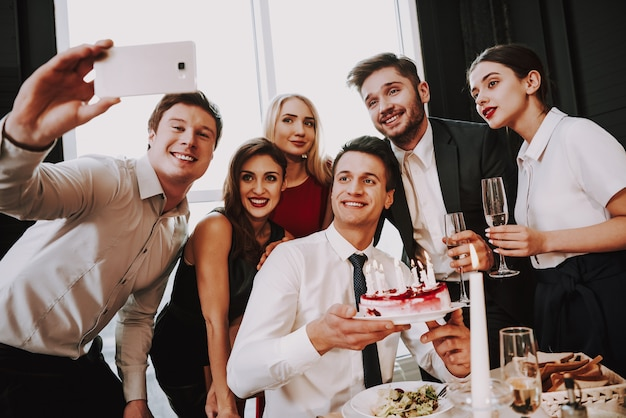 Молодая компания делает селфи на день рождения друзей.