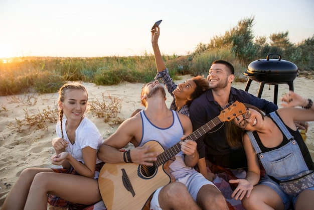 Young company of friends rejoicing, resting at beach during sunrise