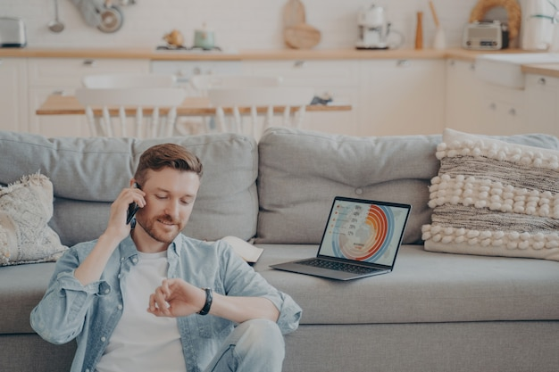 Young company male worker calling his supervisor while uploading infographics and sending them to his boss, checking time hoping he isn't late, sitting on floor while resting against couch