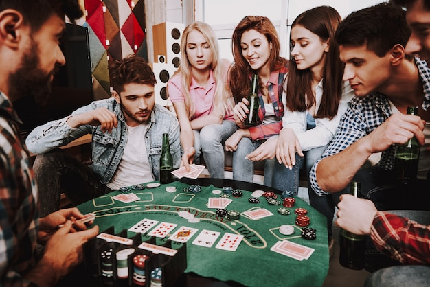 Young company playing holdem poker on a party.