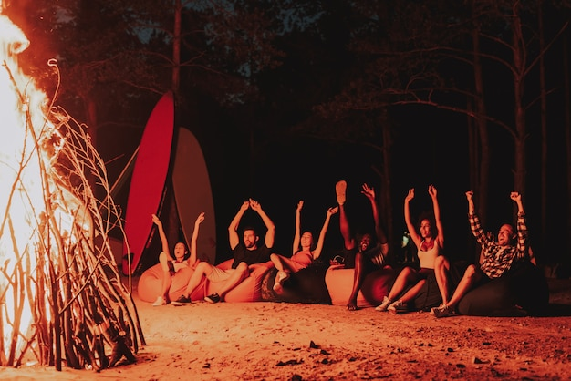 Young company sit in front of bonfire on beach.
