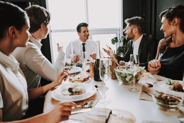 Young company sits in suits around dinner table
