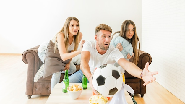 Young company watching football at sofa