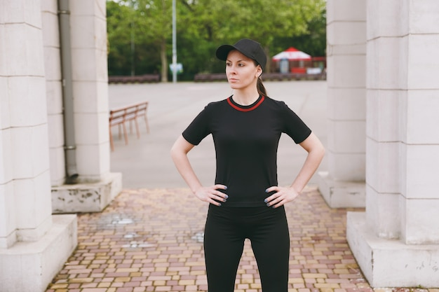 Giovane bella donna bruna atletica concentrata in uniforme nera e berretto che fa esercizi sportivi, riscaldamento prima di correre, in piedi nel parco cittadino all'aperto