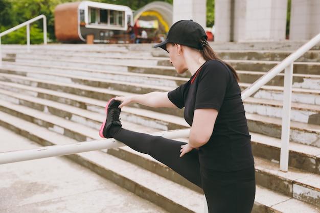 Giovane bella donna bruna atletica concentrata in uniforme nera e berretto facendo esercizi di stretching sportivo, riscaldamento prima di correre nel parco cittadino all'aperto