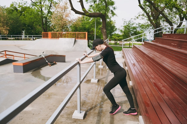 Young concentrated athletic beautiful brunette woman in black uniform, cap with earphones listening to music doing sport stretching exercises warming-up in city park outdoors