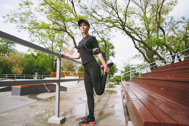 黒い制服を着た若い集中運動の美しいブルネットの女性、屋外の都市公園でウォーミングアップスポーツストレッチ運動をしている音楽を聴いているイヤホンでキャップ