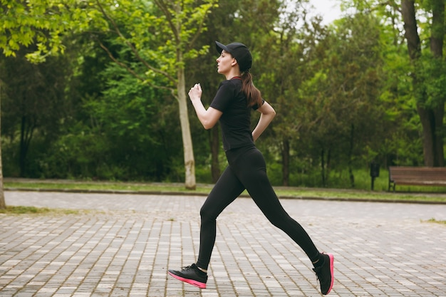 Young concentrated athletic beautiful woman in black uniform and cap training doing sport exercises running, jogging, looking straight on path in city park outdoors