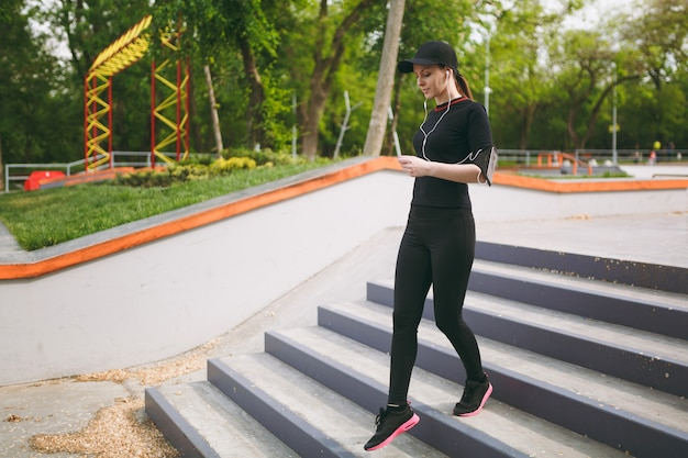 Young concentrated athletic beautiful woman in black uniform, cap with headphones doing sport exercises, warm-up before running going down on stairs in city park outdoors