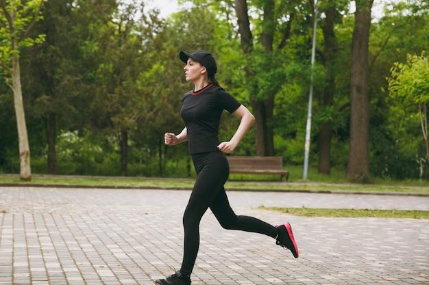 黒い制服を着た若い集中運動美女とキャップトレーニングランニング、ジョギング、屋外の都市公園の小道をまっすぐ見ているスポーツエクササイズを行う