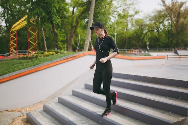 黒い制服を着た若い集中運動の美しい女性、スポーツエクササイズをしているヘッドフォンでキャップ、屋外の都市公園の階段を降りる前にウォームアップ