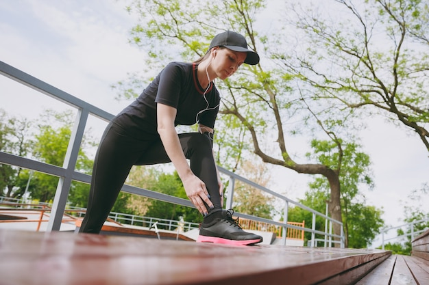 Young concentrated athletic brunette woman in black uniform, cap with earphones listening to music doing sport stretching exercises warming-up on bench in city park outdoors