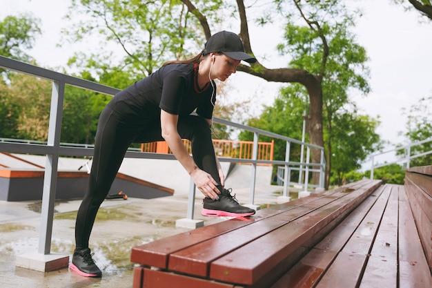 黒い制服を着た若い集中運動ブルネットの女性、屋外の都市公園のベンチでウォーミングアップスポーツストレッチ運動をしている音楽を聴いているイヤホンでキャップ