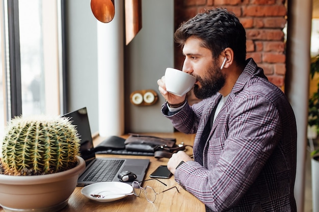 Young concentrated bearded businessman in headphones using laptop and drinking coffee latte
