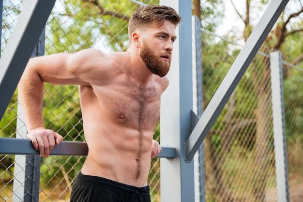 Молодой сосредоточенный бородатый сильный мужчина делает спортивные упражнения на открытом воздухе