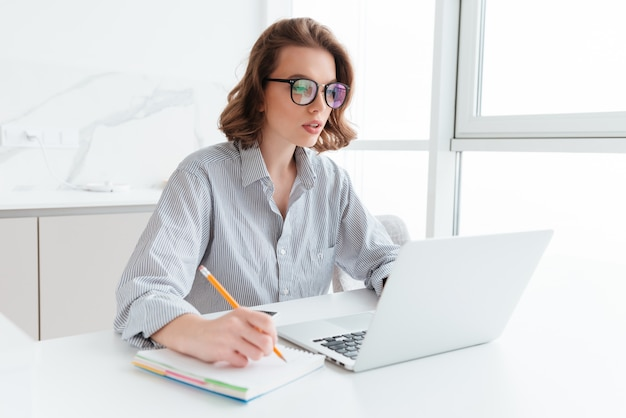Young concentrated brunette woman in glasses wokking with laptop while sitting at table in light kitchen